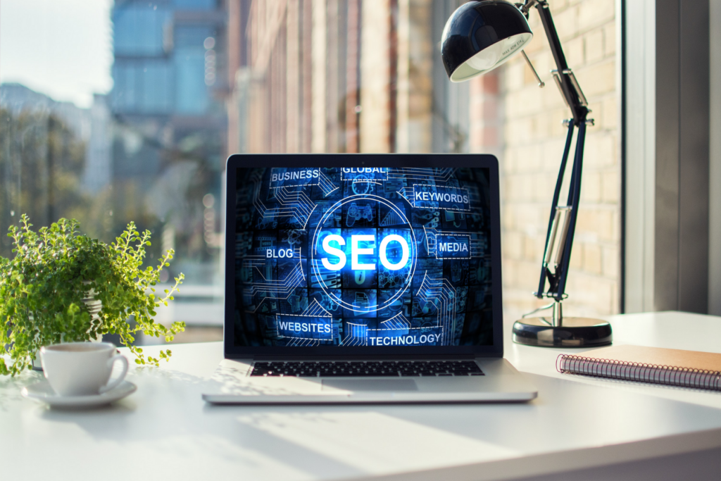 SEO benefits of having a blog, social media etc. Laptop with SEO words
